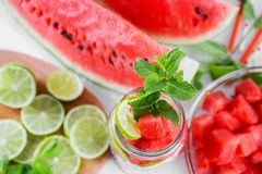 Cooking summer beverage from watermelon, lime and mint. Slices of watermelon and lime placed in a jar to fill with water royalty free stock images