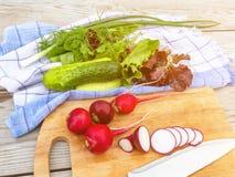 Cooking summer vegetable salad. Cutting radish close-up stock photo