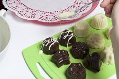 Cooking sweets with coconut and condensed milk. In a glaze of white and black chocolate.  stock image