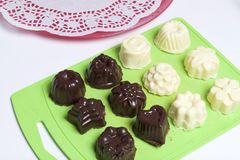 Cooking sweets with coconut and condensed milk. In a glaze of white and black chocolate.  royalty free stock photography