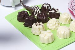 Cooking sweets with coconut and condensed milk. In a glaze of white and black chocolate.  stock images