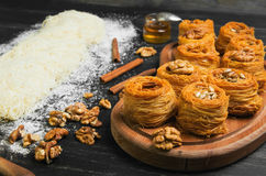 Cooking sweets turkish traditional ramadan pastry dessert kunafa. Kadaif, baklava , ingredients dough, nuts, walnuts, peanuts, sunflower seeds, honey, cinnamon Stock Photos
