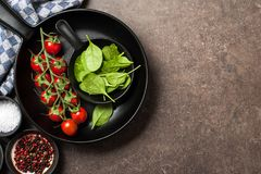 Cooking table with fresh tomatoes, spinach leaves and spices stock images
