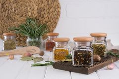 Cooking table with spices in glass jars  and herbs. On white background Royalty Free Stock Image