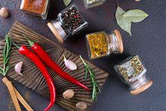 Cooking table with spices in glass jars  and herbs. On dark background Stock Images