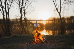 Cooking tea on a fire in a kettle at sunset royalty free stock photography