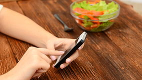 Cooking and technology - closeup of woman using a smartphone. Female using mobile phone on food table stock video