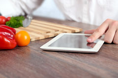 Cooking, technology and home concept - closeup of man pointing finger to tablet pc computer stock image