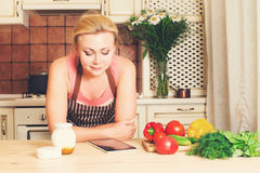 Cooking, technology and home concept. Housewife in apron with ta Royalty Free Stock Photo