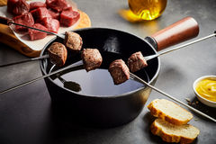 Cooking tender beef in a fondue pot Royalty Free Stock Photo