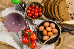 Cooking time - pan with eggs, sliced rye bread, two bowls, tomatoes and knife on canvas Royalty Free Stock Images