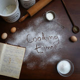 Cooking time. Text written on the flour with some ingredients around Royalty Free Stock Images