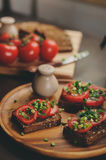 Cooking toast sandwiches with fresh tomato, green onion and wholemeal bread in dark rustic interior Royalty Free Stock Image