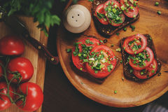 Cooking toast sandwiches with fresh tomato, green onion and wholemeal bread in dark rustic interior Royalty Free Stock Photography