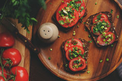 Cooking toast sandwiches with fresh tomato, green onion and wholemeal bread in dark rustic interior Stock Image