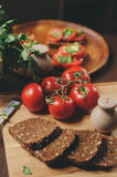 Cooking toast sandwiches with fresh tomato, green onion and wholemeal bread in dark rustic interior Stock Photos