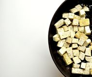 Cooking tofu in a pan on a white background Royalty Free Stock Photography