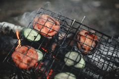 Cooking tomatoes and cucumbers at the stake. Closeup shot of roasted tomatoes and cucumbers at the stake royalty free stock image