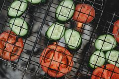Cooking tomatoes and cucumbers at the stake. Roasting tomatoes and cucumbers at the stake royalty free stock photo