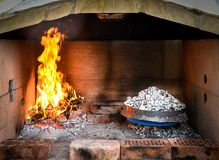 Cooking of traditional Balkan Greek Mediterranean Croatian meal. Peka in metal pots called sac sach or sache or a metal lid. Fireplace with open fire and Royalty Free Stock Images