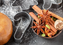 Cooking traditional biscuits and gingerbread. Christmas. New year. Cutting the cookies and the spices on the table. Cinnamon sticks, cardamom, nutmeg, star Stock Images