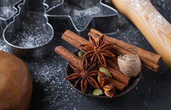 Cooking traditional biscuits and gingerbread. Christmas. New year. Cutting the cookies and the spices on the table. Cinnamon sticks, cardamom, nutmeg, star Stock Image