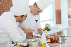 Cooking trainees preparing dishes. Chef training students in restaurant kitchen Royalty Free Stock Image