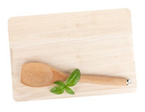 Cooking utensil and basil leaves over cutting board Stock Photos