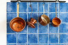 Cooking utensils. Ancient copper cookware, Blue tiles wall background. Stock Photography