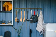 Cooking utensils hanging on wooden wall in the kitchen. Transparent glass jars for grain stock photo
