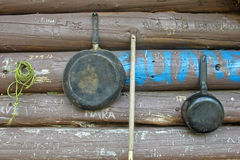 Cooking Utensils and log cabin. Frying pan & pot hanging on log cabin wall covered in graffiti Stock Photos