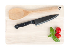 Cooking utensils and tomato with basil over cutting board Royalty Free Stock Image
