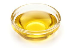 Cooking vegetable oil in a small, glass cup, isolated on white background.  Royalty Free Stock Photo