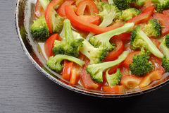 Cooking vegetables. Close-up cooking pepper and broccoli with oil royalty free stock images