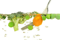 Cooking vegetables. Vegetables, carrots, peas and brocolli cooking in boiling water stirred with a fork royalty free stock photo