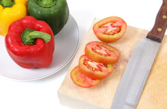 Cooking vegetables. Closeup image of fresh pepper tomato and knife on white table Royalty Free Stock Image