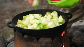 Cooking of vegetables in cauldron outdoors stock video footage