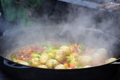 Cooking vegetables in large cast iron cauldron Stock Photo
