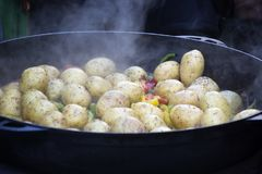 Cooking vegetables in large cast iron cauldron Royalty Free Stock Photo
