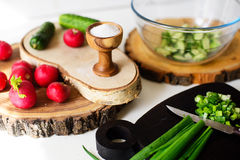 Cooking vegetables salad. Wooden salt cellar and fresh vegetables prepared for cooking a salad Stock Photos