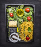 Cooking and vegetarian concept pasta with cheese, colorful spices, herbs, butter and a small grater in a black wooden tray on wood Stock Image