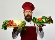 Cooking and vegetarian diet concept. Cook with shocked face. In burgundy uniform holds salad ingredients. Chef holds board with fresh vegetables on board and Royalty Free Stock Image