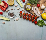 Cooking vegetarian food oil, mushrooms, cherry tomatoes on a branch, cucumber, pepper, seasoning on wooden rustic background top v. Cooking vegetarian food oil Royalty Free Stock Photos