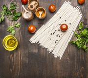 Cooking vegetarian noodles with cherry tomatoes, herbs and spices and oil on a wooden background, noodles lies in  vintage pot sp Stock Images