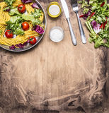 Cooking vegetarian pasta with salad and vegetables, oil and salt for food appliances border ,place text  on wooden rustic back Royalty Free Stock Image