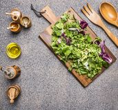 Cooking vegetarian salad with herbs, butter,salt, pepper mill, a wooden spoon and fork for the salad on wooden rustic background. Cooking vegetarian salad with Stock Photo