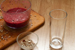 Cooking vivid smoothie ingredients in blender and seeds. On wooden royalty free stock photo