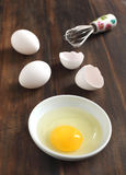Cooking, whisk with eggs in a bowl and egg shells Royalty Free Stock Images
