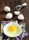 Cooking, whisk with eggs in a bowl and egg shells. On a wooden table Stock Images