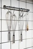 Cooking whisks. Hanging in a restaurant kitchen royalty free stock images